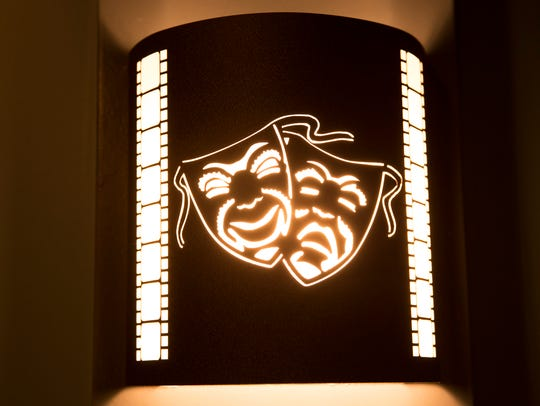 A wall sconce with a theatrical motif  in a high-end