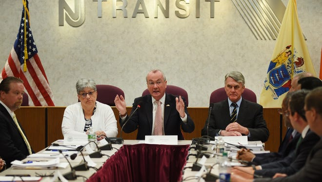 Gov. Phil Murphy speaks as Dianne Gutierrez-Scaccetti (L), Commissioner of Transportation, Kevin Corbett (R), Exec. Director of NJ Transit and senior staff members from NJ Transit Management, listen during an NJ Transit briefing at the NJ Transit Headquarters in Newark on 08/09/18. This is his first public appearance since the agency experienced major delays and cancellations while he was on vacation.