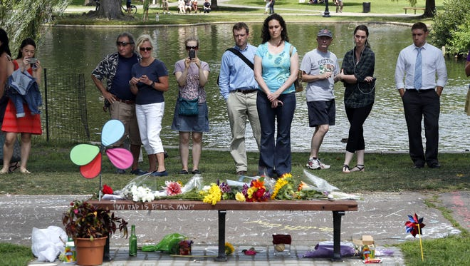 """People pause by a bench at Boston's Public Garden, Tuesday, Aug. 12, 2014, where a small memorial has sprung up at the place where Robin Williams filmed a scene during the movie, """"Good Will Hunting."""" Williams, 63, died at his San Francisco Bay Area home Monday in an apparent suicide."""