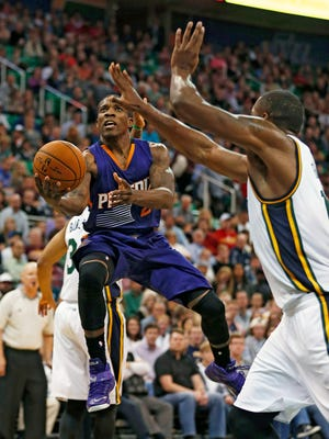 Phoenix Suns' Eric Bledsoe, left, lays the ball in past Utah Jazz' Derrick Favors during the first half of an NBA basketball game in Salt Lake City, Saturday, Nov. 1, 2014.