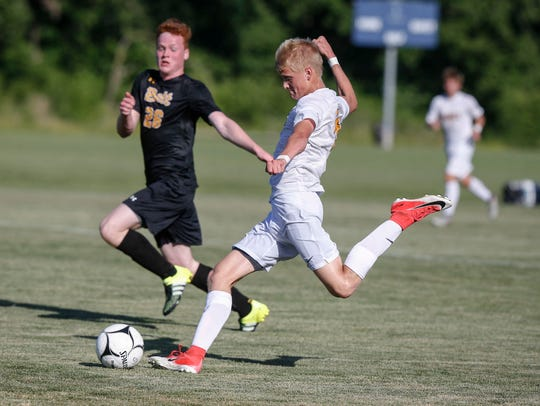 Ankeny junior Charlie Pritchard kicks the ball toward