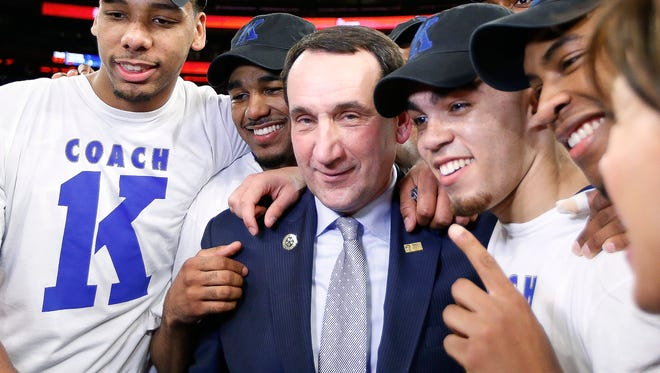 Duke coach Mike Krzyzewski, center, celebrates with his players after his 1,000th career win, Sunday against St. John's at Madison Square Garden.
