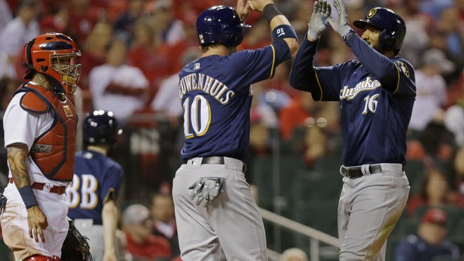 Milwaukee Brewers' Domingo Santana (16) celebrates at home plate with teammate Kirk Nieuwenhuis (10), as St. Louis Cardinals catcher Yadier Molina (4) looks on, after hitting a two-run home run in the ninth inning.