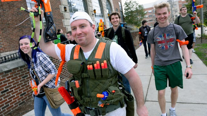 Evan Filipiak salutes with his Nerf gun as he seeks reinforcements during a weeklong zombie apocalypse version of tag involving Michigan State University students in East Lansing.