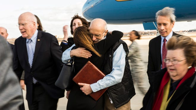 Alan Gross greets an entourage of family and friends awaiting his return from five years of captivity in Cuba on Dec. 17. U.S. Sen. Patrick Leahy is seen at left.