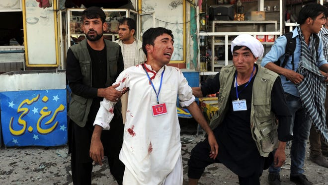 People help an injured victim after a suicide bomb attack that targeted a demonstration of Afghanistan's Hazara minority in Kabul on July 23, 2016.