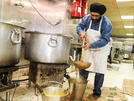 Inderpal Singh pours some dal into serving buckets