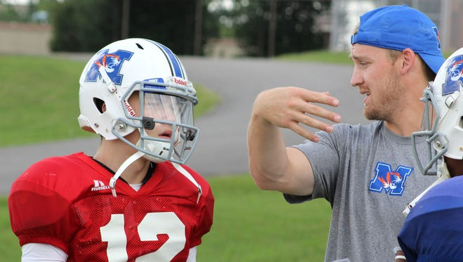 Marshall County quarterbacks coach Bo Wallace, right, gives his brother Bryce instructions during a drill.