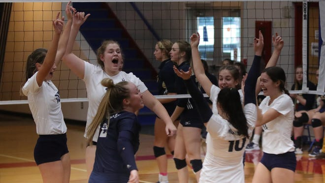 The TMP-Marian volleyball team celebrates a point during Saturday's Sub-State final vs. Phillipsburg in Russell.