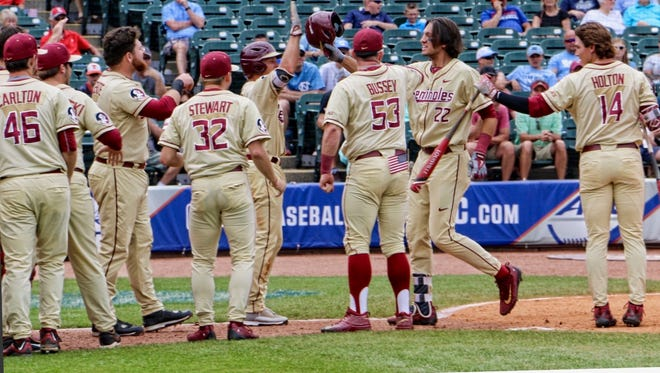 Florida State freshman Drew Mendoza is congratulated by his teammates after hitting a three-run homerun during the eighth inning of the Seminoles 7-3 victory over North Carolina n the ACC Tournament title game on Saturday afternoon at Louisville Slugger Field.