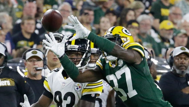 Green Bay Packers' Josh Jackson intercepts a pass in front of Pittsburgh Steelers' Damoun Patterson and returns it for a touchdown during the second half of a preseason NFL football game Thursday, Aug. 16, 2018, in Green Bay, Wis.