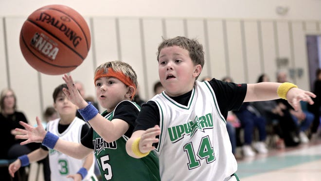 Wyatt Ivey, left, and Major Deitch battle for a loose ball during their game in a Upward Sports Program basketball league. The program teaches kids the fundamentals of the game, as well as teamwork and sportsmanship.