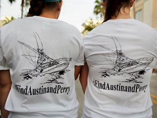 Girls wear t-shirts they bought at to help fund the ongoing private search for Nick Cohen and Austin Stephanos who have been missing since they took their boat out of the Jupiter Inlet, Friday, during a fundraiser at Jumby Bay Island Grill, Wednesday, July 29, 2015, in Jupiter, Fla.