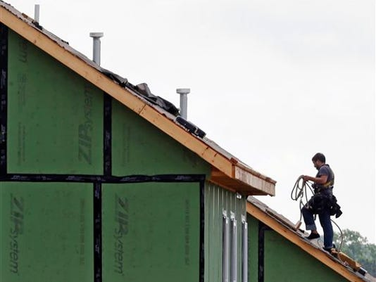 In this photo taken Tuesday, June 9, 2015, a roofer works on a home under construction in the Briar Chapel community in Chapel Hill, N.C.