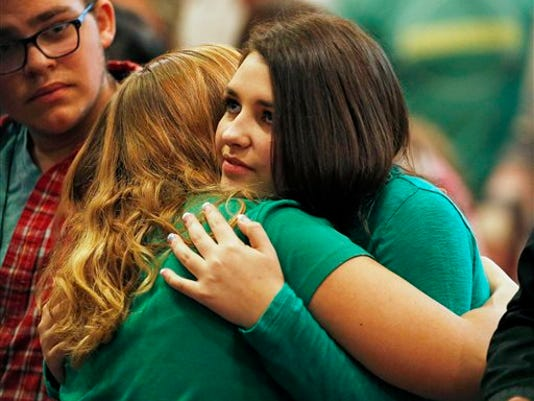Lacey Scroggins, right, receives a hug during a church service at the New Beginnings Church of God Sunday, Oct. 4, 2015, in Roseburg, Ore. Scroggins is a survivor of the fatal shooting at Umpqua Community College.