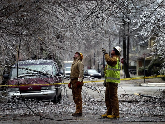 Electric line workers Eddie McCardle, right, and R.J.