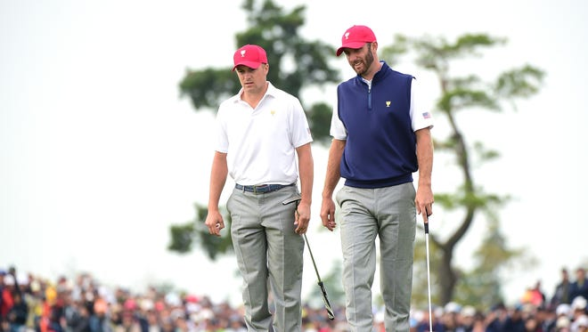 Jordan Spieth (L) and Dustin Johnson of the United States Team line up a putt on the 18th green during the Saturday foursomes matches at The Presidents Cup at Jack Nicklaus Golf Club Korea on October 10, 2015 in Songdo IBD, Incheon City, South Korea.