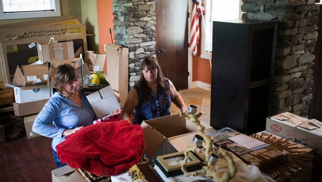 """Darlene Eherenman, of Warsaw, Indiana, left, helps her twin sister Arlene Nickless pack Sunday, May 21, 2017.  Arlene Nickless and her family have to be out of their Holt home by Monday, May 29, 2017.  The home was rebuilt from the ground up in 2008 by """"Extreme Makeover: Home Edition"""" after her husband Tim died."""