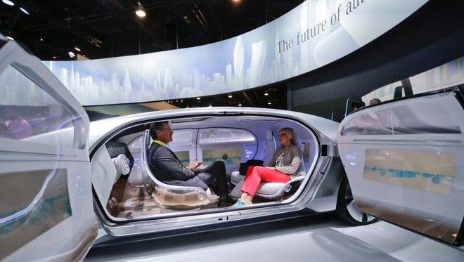 Attendees sit in the self-driving Mercedes-Benz F 015 concept car at the Mercedes-Benz booth at the International CES show in Las Vegas.
