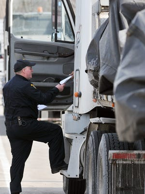 Don Dailey, Commercial Motor Carrier Inspector for the Ohio Highway Patrol, checks the paperwork of a driver at the US 30 rest stop West of I-71 Friday, February 19th.