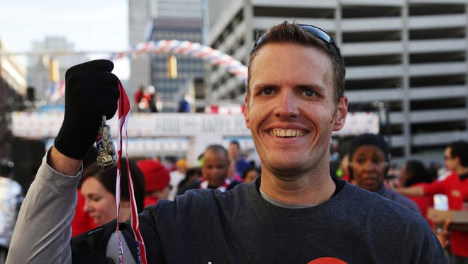 Brian Flemming, 32, of Canton, holds his medal after completing the half marathon during the 37th Annual Detroit Free Press/Talmer Bank Marathon in Detroit on Sunday, Oct. 19, 2014. Flemming finished his first half marathon after losing almost 400 lbs.