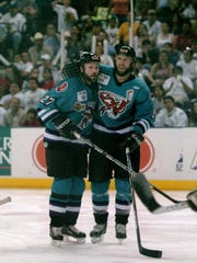 Former Bossier-Shreveport Mudbugs Trevor Buchanon (27) and David Oliver embrace during the 2004 Presidents Cup Final.
