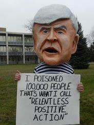A protester parodies Michigan Gov. Rick Snyder during