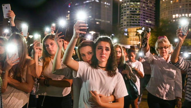 Mary Claire Foley, center left, 16, embraces Ariana Skafidas, 16, students at Henry B. Plant High School at Curtis Hixon Park in downtown Tampa, Fla., Monday, Feb. 19, 2018, as they raise their lights during a vigil to honor victims of Wednesday's shooting at Marjory Stoneman Douglas High School in Parkland, Fla.