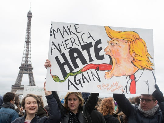 """People hold a banner reading """"Make America hate again"""""""
