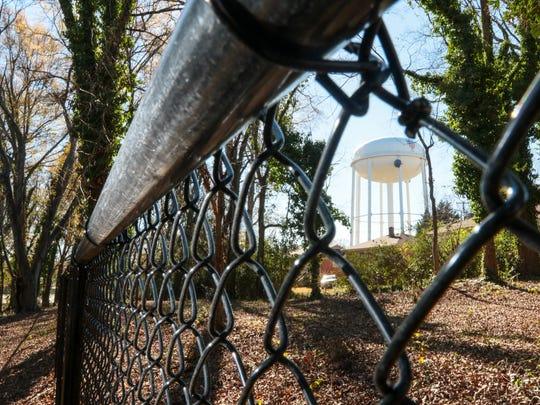 A fence at the future home of TBA Dog Park along Fant Street is not completely enclosed, seen near a water tower at the Anderson County Main Library in Anderson.
