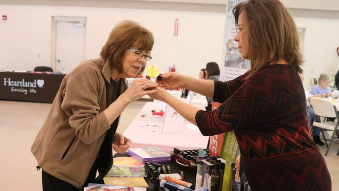 Jean Drafahl, of Woodville, tries out the melaleuca essential oil from Brenda Kolhoff, wellness advocate for doTerra Oils, at the 'Loving Life' health and beauty expo in Elmore.