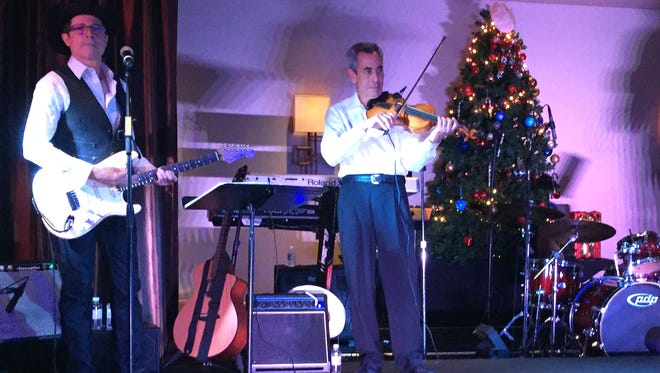"""Professional fiddle player and bass guitar player play for """"Heart of the Holidays"""" at the Eureka Casino Resort Tuesday night."""