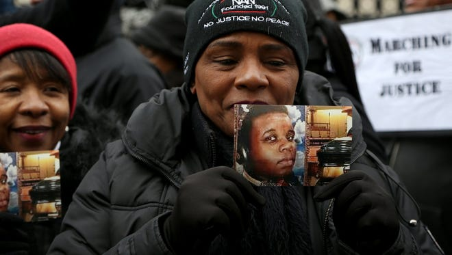Holding a picture of Michael Brown, Virginia Williams, 56 of Romulus joined other protesters across the street from the Theodore Levin United States Courthouse in downtown Detroit today.