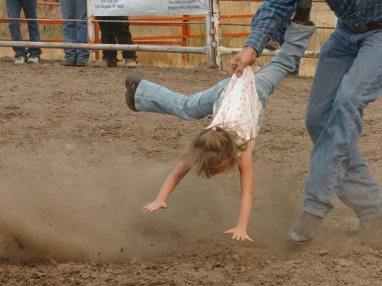 Jayd Finlayson gets a mid-air rescue after she lost her grip on the sheep she was riding Thursday in the junior rodeo at the 2007 Chouteau County Fair.