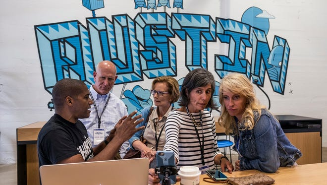 During a tour of Google Fiber in Austin, Texas, web developer Arvin Poole, left, talks about a software program with Univerisity of Louisville official Harlan Sands, JCPS Superintendent Donna Hargens, JCPS board member Steph Horne and Metro Councilwoman Angela Leet, right.