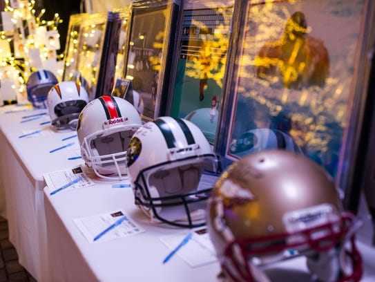 Signed NFL helmets sit out for auction during the YMCA's