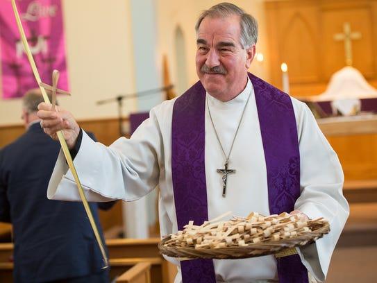 Pastor Fred Schenker walks down the aisle of St. Paul's
