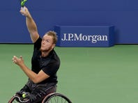 FILE - In this Jan. 27, 2018, file photo, France's Stephane Houdet reaches for a forehand return to Japan's Shingo Kunieda in the men's wheelchair final at the Australian Open tennis championships in Melbourne, Australia. There might be wheelchair tennis competition at the 2020 U.S. Open, after all. The U.S. Tennis Association now says it should have consulted wheelchair athletes before announcing it was canceling their events at Flushing Meadows and is willing to change its stance. (AP Photo/Vincent Thian, File)