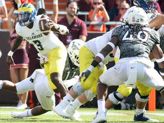 Delaware quarterback Joe Walker is hit by Virginia Tech's Houshun Gaines in the second quarter at Lane Stadium in Blacksburg, Va. Saturday.
