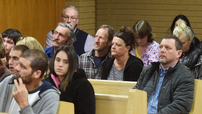 Audience members watch arraignment hearings on a large screen TV during a recent session of Baxter County Circuit Court.