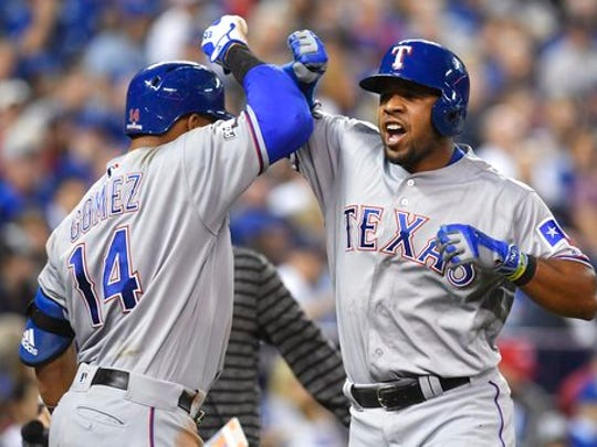FILE - In this Oct. 9, 2016, file photo, Texas Rangers' Elvis Andrus, right, celebrates his solo home run with teammate Carlos Gomez during  the third inning in Game 3 of the American League Division Series in Toronto. Now that the Cubs have broken baseball's oldest curse, who's next? No team from Texas has ever won the World Series.