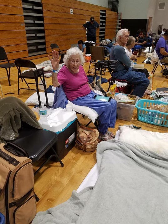 Edith Rood waves from the shelter at South Fort Myers High School. -