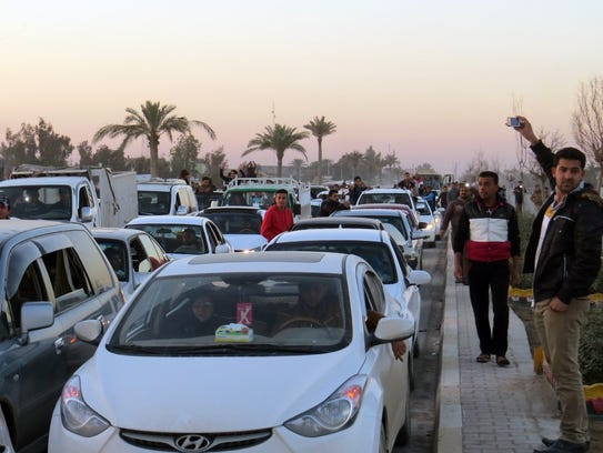 Iraqis drive their vehicles early on Dec. 29, 2015,