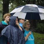 Neighbors watch as John Wienges and Will Lenski rescue their neighbors from their flooded homes along Gills Creek. The river flooded homes along Timberlane Drive and Whispering Pines Circle.