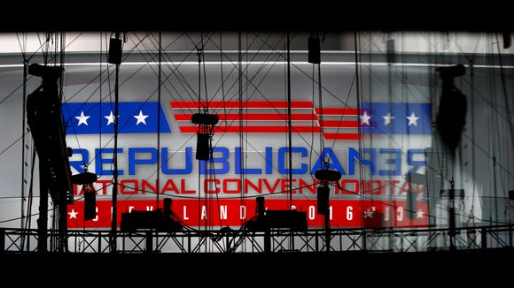A Republican National Convention logo is seen though silhouetted production equipment on a huge video screen at Quicken Loans Arena for the Republican National Convention, Sunday, July 17, 2016, in Cleveland. (AP Photo/Carolyn Kaster)