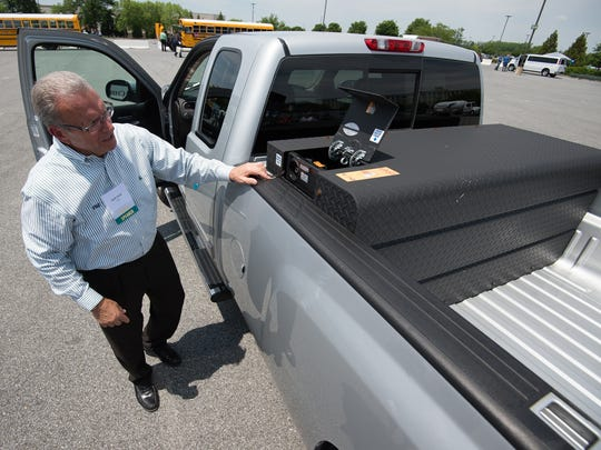 Jack Stull, regional field sales manager for VNG, with a Chevy Silverado 2500 outfitted with a natural gas fuel tank during an alternative fuels workshop at Dover Downs Casino in Dover.
