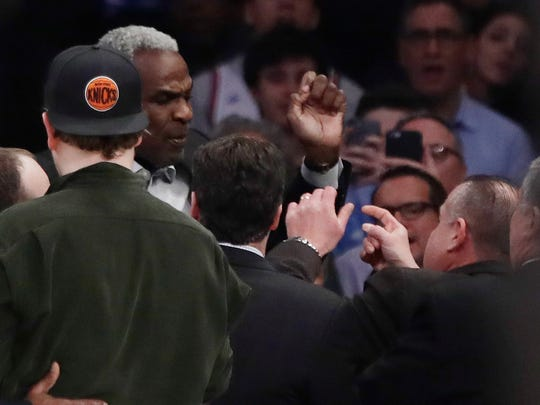 Former Knicks player Charles Oakley exchanges words with a security guard during Wednesday's game at MSG.