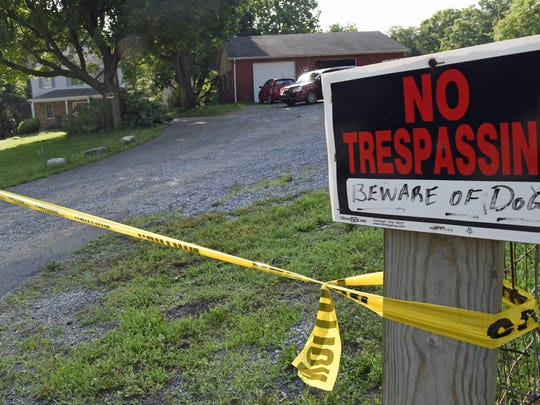Police tape surrounds a Welsh Run Road property where three people were fatally shot on June 25, 2016.