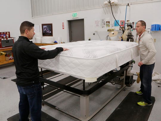 Merrick Steinmetz, left, and Jonathan Fields rotate a mattress before using a tape edge machine for the final stitching Thursday, February 22, 2018, at Holder Bedding Mattress Factory, 230 Farabee Drive in Lafayette.