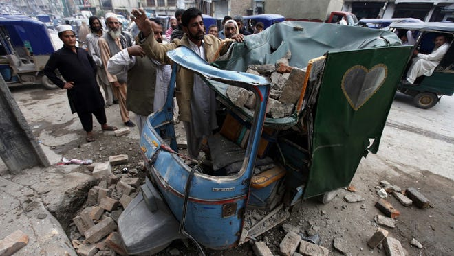 People remove debris from a rickshaw on a road following an earthquake in Peshawar, Pakistan, on Monday, October 26, 2015.
